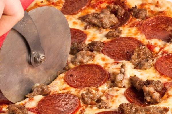 photo of meatlovers pizza being cut