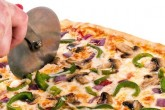 photo of veggie pizza being cut
